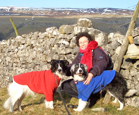The dogs cuddling up to Rachael and keeping warm in their dog jumpers up on the hills